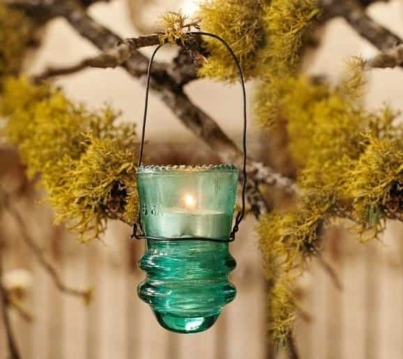 Vintage Glass insulators become beautiful tea-light outdoor lamps. Just add some old wire that you twist around and create a long handle - be sure to create enough clearance to avoid fires.