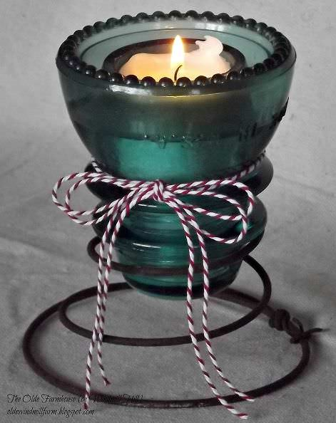 Transform Vintage Glass insulators into adorable candle holders using a mattress spring. It coils around the tapered top of the insulator perfectly.