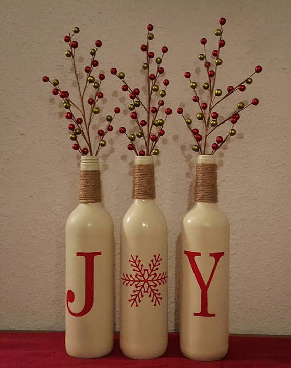 Spread joy with your Christmas Decor by upcycling wine bottles and decorating them with stencils, jute, and paint.
