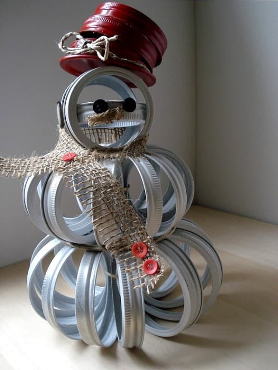 An upcycled canning jar lid snowman is another great Upcycled Christmas Ideas for your home.