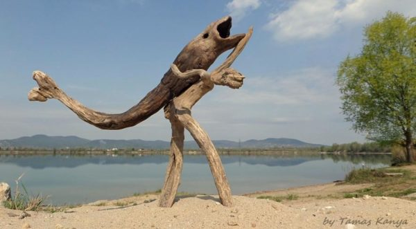 A twisted Driftwood Art man carries a large fish.